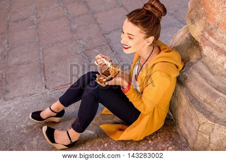 Young woman eating tiramisu, traditional italian dessert, on the street in Bologna city in Italy. Tiramisu was invented in Veneto region in Italy. Soft focus with small depth of field