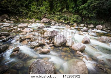 Water of the Mossman River flows over ancient rocks and boulders in Mossman Gorge, Queensland, Australia poster
