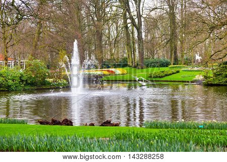 Lisse, Netherlands - April 4, 2016: Lake and fountain in the spring flower garden and Keukenhof park view