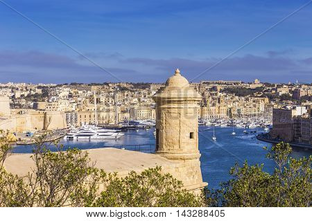 Malta - Watch tower of Valletta with Senglea and Gardjola Gardens at background on a sunny afternoon
