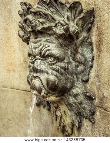 Old face spout gargoyle on an exterior wall