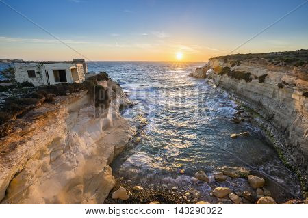 Malta - Sunrise near St.Thomas bay with weekend cabin and clear blue sky