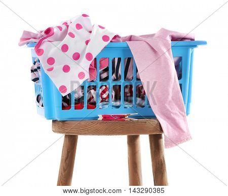 Blue plastic basket with baby laundry on white background