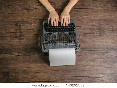 Woman hands working with retro typewriter on wooden background