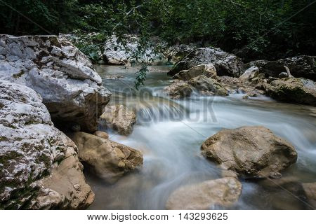 beautiful natural wild mountain creek flowing between rocks