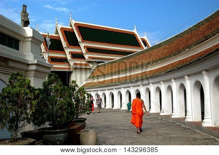 Nakhon Pathom Thailand - December 27 2005: A Buddhist monk in orange robe walking along an arched colonnade and the west Vihara at Wat Phra Pathom Chedi