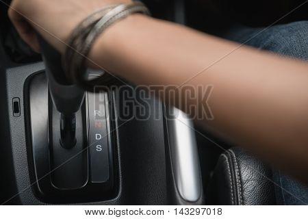Image of pulling handbrake on the car,focus  on the gear motor.