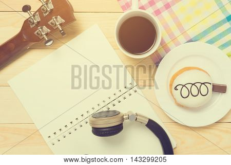 Music writing chilling relax top view equipments. Guitar Blank note book Music headphone and Coffee for Music writing concept background.