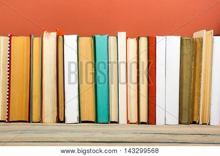 Colorful composition with vintage old hardback books, diary on wooden deck table and red background. Books stacking. Back to school. Copy Space. Education background