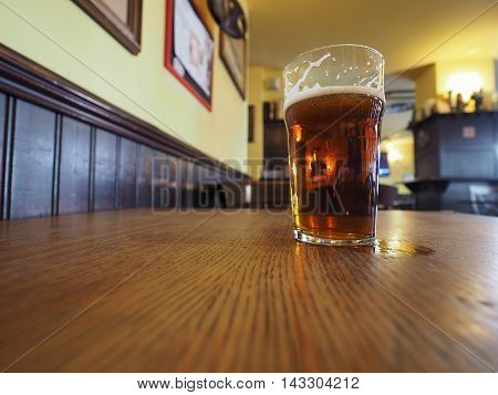 A pint of British ale beer on a pub table wide angle view with copy space