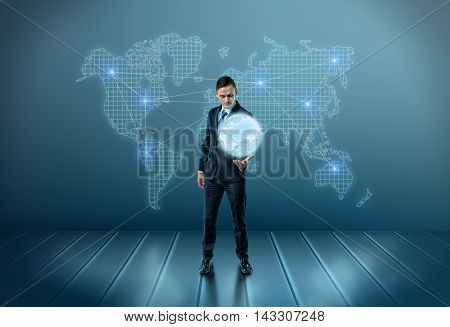 Businessman holding a glowing world globe as he stands in front of a map on the wall with a network of interconnected blue lights across the continents in a conceptual image