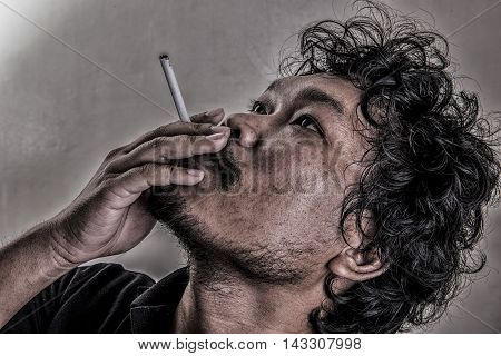 The man with the cigarette. The smoke from the cigarette in his hands (Retro style)