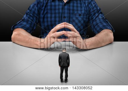 Businessman with bowed head stands in front of a cropped portrait of a big man sitting with his fingers clasped. Business staff. Boss and employee. Implicit obedience. Guilt and humiliation.