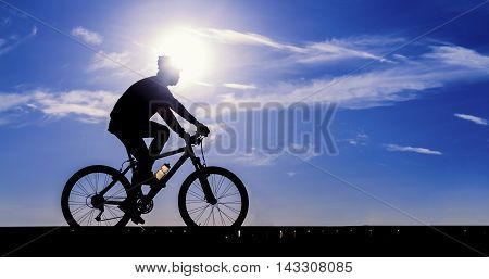Silhouette of the cyclist riding a road bike