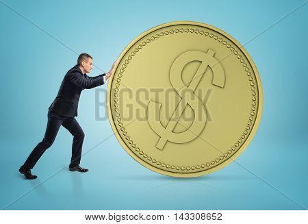 Businessman rolling big golden dollar coin. Money and wealth. Hard work. Successful management. Economy and finance.