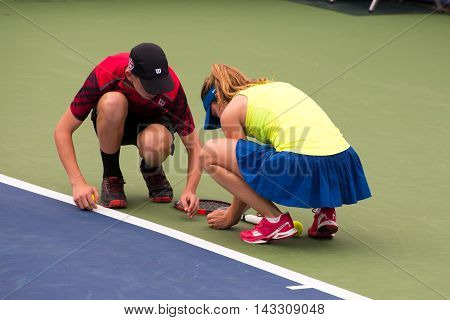 Mason Ohio - August 13 2016: Alize Cornet stops play and is helped by a ball boy to move a bug off the court in a qualifying match at the Western and Southern Open in Mason Ohio on August 13 2016.