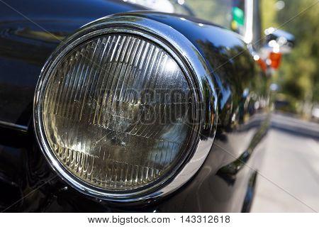 Detail of an attique car at a retro car parade. Headlights. Black headlamp.