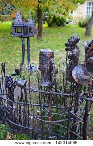 MOSCOW - SEP 22, 2015: Wicker fence with rooster and jug made of iron in city garden in VDNH