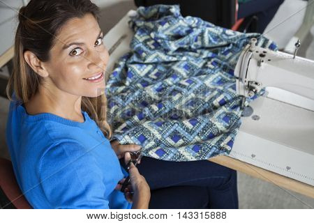 Confident Tailor Cutting Fabric At Workbench