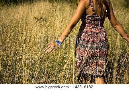 Young beautiful girl walking in the field and runs a hand through the high dry grass at summertime.