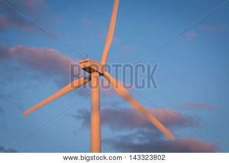 A wind turbine spins in the early morning hours.