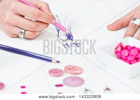 Fashion designer sketching purple prom dress, toned image