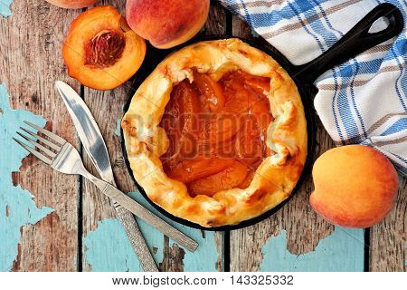 Delicious Peach Tart In Cast Iron Baking Skillet, Scene From Above Over Rustic Wooden Background