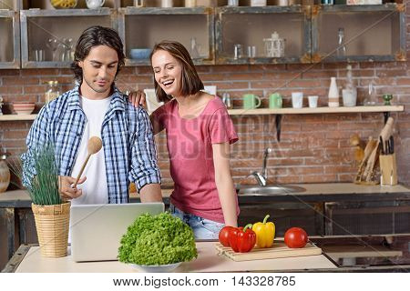 Happy married couple is deciding what to cook. They are reading recipe on laptop with interest. Woman is embracing man and laughing