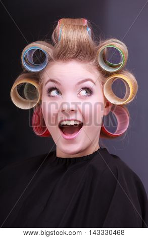 Portrait of funny happy woman in beauty salon. Cheerful blond girl with hair curlers rollers by hairdresser. Hairstyle.