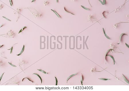 frame with dry flowers branches leaves and petals on pink background. flat lay top view