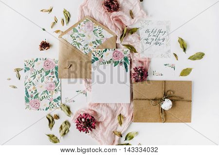 Workspace. Wedding invitation cards craft envelopes pink and red roses and green leaves on white background. Overhead view. Flat lay top view