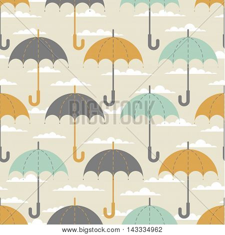 Seamless texture. Autumn. Depicts the umbrellas of the same size .Umbrella in three colors : grey, yellow and blue .Umbrellas in the clouds. Umbrellas on a beige background.