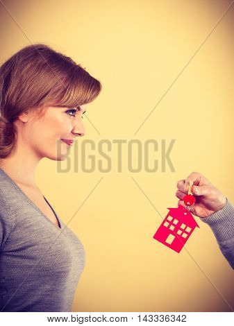 Male hand real estate agent or husband giving woman wife new house key keys to property owner. Housing loan concept.