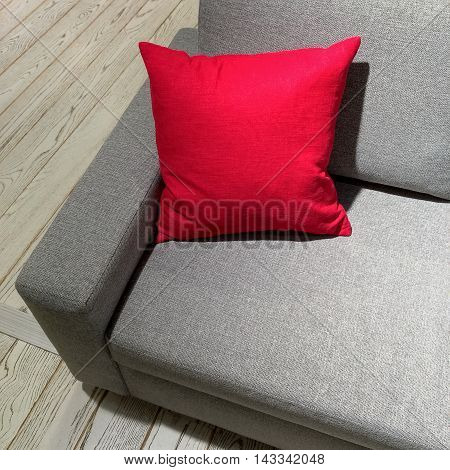 Classic gray sofa with vibrant red cushion. Modern furniture.