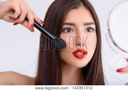 Carefree girl is applying blush on her cheek with concentration. She is standing and holding small mirror. Isolated