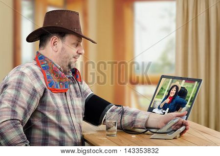 Virtual rural doctor takes cowboy patients blood pressure online. Female physician gives thumb up and looks at him from monitor. Mature man with brown hat, checkered shirt, red neckerchief sits at wooden table and checks his blood pressure before taking p