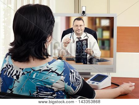 Experienced cardiologist sits face to face with online female patient which measures her blood pressure. Handsome virtual doctor attentively reviews brain x-ray results with her. Horizontal shot on blurry indoors background