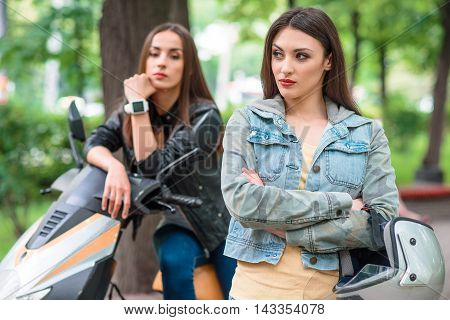 Two girls had a quarrel. Woman is standing and looking aside with offence. Her friend is sitting on bike in park with sadness