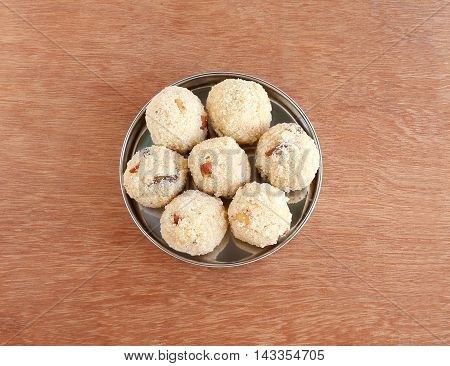 Indian sweet food rava laddu, which is a traditional and popular dish is made from semolina, raisins, almonds and sugar, in a steel plate. This sweet item is usually made for festivals like Diwali.
