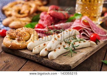 Glass Of Beer, Pretzels And Various Sausages On Wooden Background. Oktoberfest.