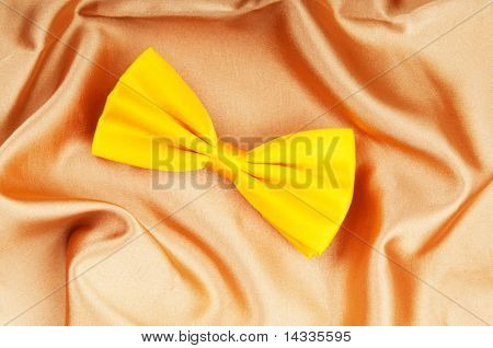 Bow ties on the bright satin background
