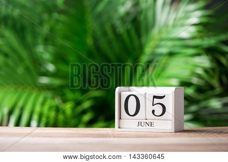 World Environment Day. June 5th. Image of june 5 wooden color calendar on green background.