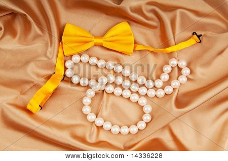 Bow ties and pearl necklace on the satin