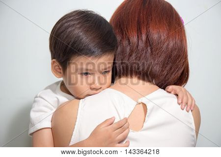 close up 3 years old Asian kid hug his mother on white background