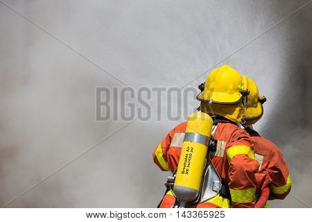 two firefighter in fire fighting suit spraying high pressure water to fire and smoke