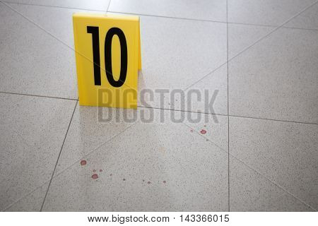 evidence marker at bloodstain on room floor in crime scene training course