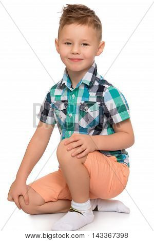 Nicely combed little boy in a plaid shirt and pink shorts is kneeling on the floor - Isolated on white background