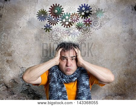 Bewildered looking man is releasing a thought train of cog wheels. Concerned facial expression. Both hands clasping head in a desperate gesture. Decaying background wall with textured surface.