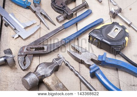 Construction tools on wooden background. Copy space for text. Set of assorted work tools at wood table . Top view.