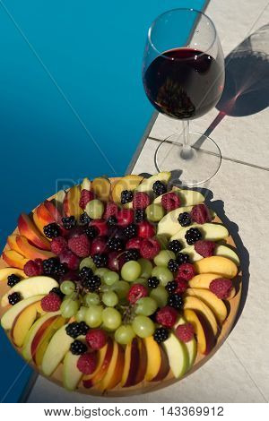 Fruit and berry platter with juicy ripe fresh tasty vibrant natural colorful dessert peach grape apple near glass of red wine on background of blue water copy space